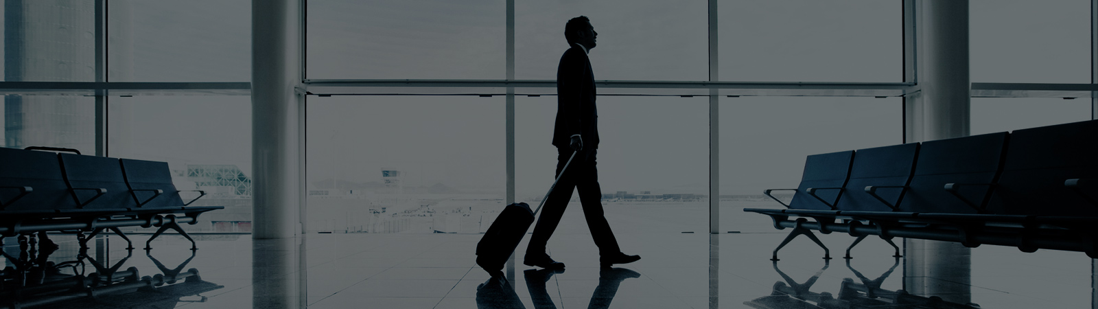 A man walking in an airport with his suitcase